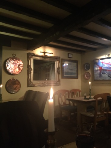 Copper pans and ornage mirror at the John Barleycorn pub in Duxford